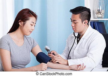 Asian doctor taking blood pressure of a patient