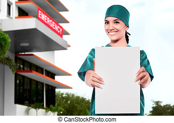 Asian Doctor woman showing blank paper in front of the emergency room