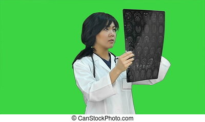 Asian doctor woman using digital tablet and smiling on a Green Screen, Chroma Key