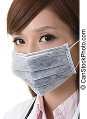 Asian doctor woman wear a surgical mask, closeup portrait.