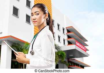 Asian Doctor woman with stethoscope holding a clipboard in front of the emergency room