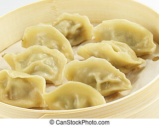 These Chinese dumplings (jiaozi) are filled with meat, cabbage, and other seasonings, then steamed or boiled. Traditionally eaten during Chinese New Year.