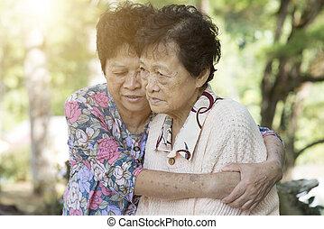 Asian elderly women hugging