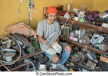 asian electronics repairman holding fan while sitting around broken items