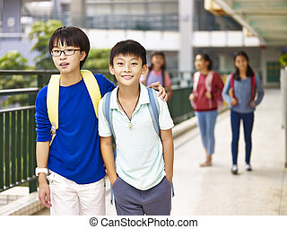 asian elementary school student walking on campus
