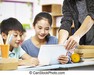 asian elementary schoolchildren using digital tablet in classroom
