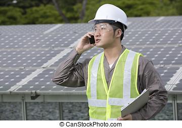 Asian engineer checking solar panel setup.