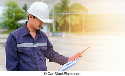Asian engineer in safety uniform and white helmet holding a clipboard and walkie-talkie on blurred industry plant background