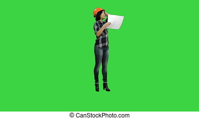 Asian engineer woman woring with construction plan on a Green Screen, Chroma Key