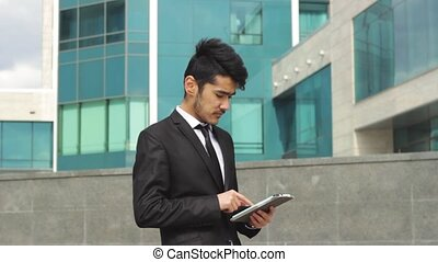 Asian ethnic businessman working on tablet