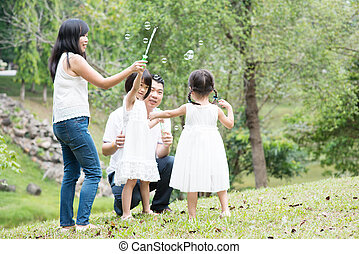Asian family blowing soap bubbles at park