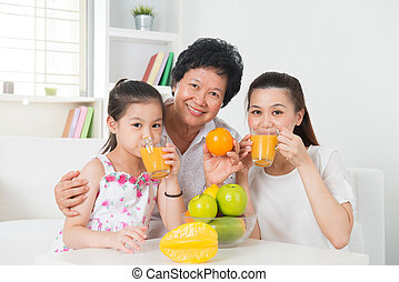 Asian family drinking orange juice.
