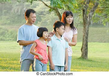 Asian Family Enjoying Walk In Summer Countryside