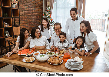 family fun having lunch with friends in diningroom together...