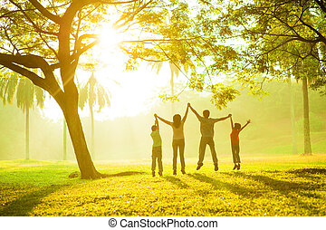 Rear view of joyful Asian family jumping together in the park