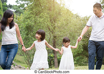 Asian family hold hands and walking at outdoor park.