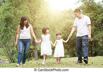 Asian family hold hands walking at outdoor park.