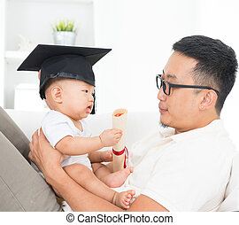 Baby with graduation cap holding certificate