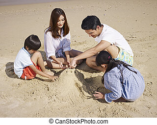 asian family on beach - asian family with two children...