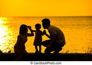 Asian family outdoor sunset beach