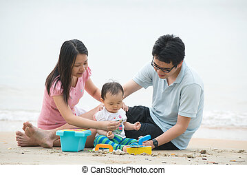 asian family playing on the beach