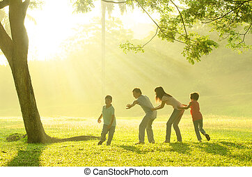 asian family playing with joy in park during a beautiful morning