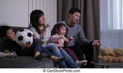 Close-up of excited chinese family with little kids upset with favorite football team losing while watching match on TV at home. Sad soccer fans disappointed during football game