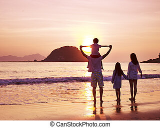 asian family watching sunrise on beach