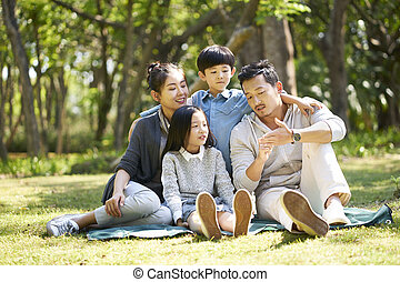 asian family with two children chatting park