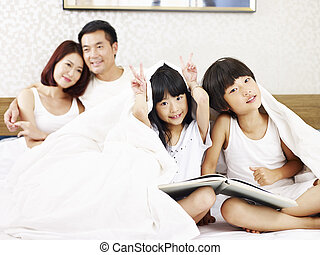 asian family with two children having fun in bedroom