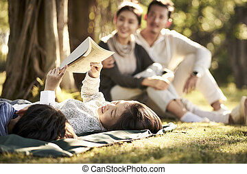 asian family with two children relaxing in park