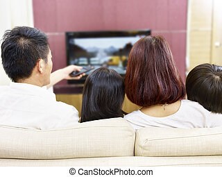 asian family with two children watching TV together