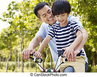 asian father and son enjoying biking outdoors