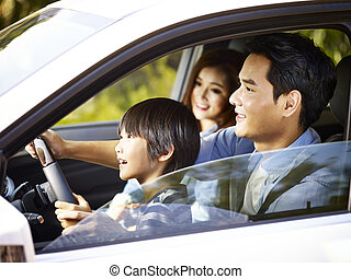 asian father letting son hold the steering wheel