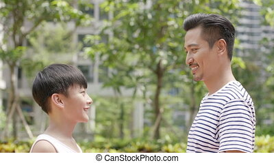 Asian father & son cheering after score during basketball...