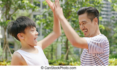 Asian father & son giving a high five after scoring outdoors in morning