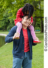 Asian father with daughter in park
