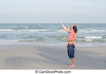 father with his child standing on the beach