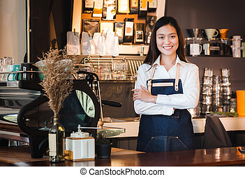 Asian female barista wear jean apron crossed her arms at counter bar with smile face, cafe service concept, owner business start up
