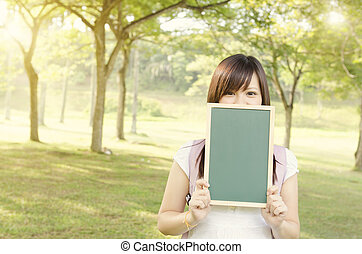 Asian female college student showing blank chalkboard