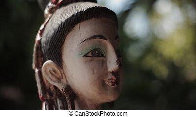 Asian female cracked statuette. Pan vertical. Idol, culture,...