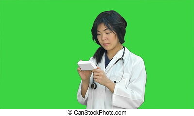 Asian female doctor reading prescription and looking at box of medicine on a Green Screen, Chroma Key