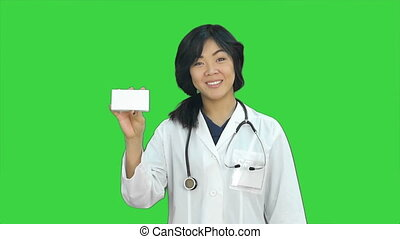 Asian female doctor showing a bottle of tablets looking at camera on a Green Screen, Chroma Key