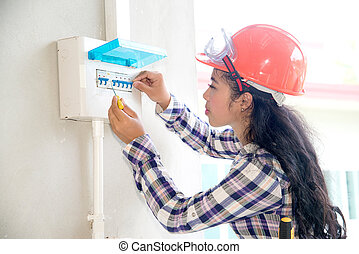 Asian female Electrician or Engineer check or Inspect Electrical System circuit Breaker on Power Distribution panel at home.