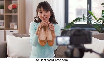 asian female fashion blogger making video of shoes -...