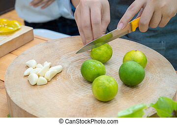Asian female holds orange knife to slide green lemon lime on the wood circle plate with garlice beside.