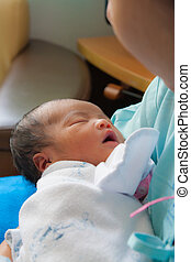 Asian female newborn in mother's arms vertical