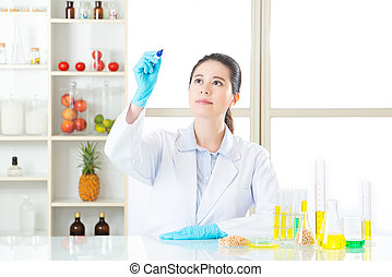 Asian female scientist recording the result on writing glass