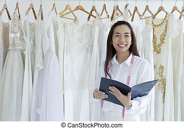 Asian female smilling of bridal store owner with a diary.
