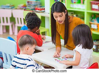 Asian female teacher teaching mixed race kids reading book...